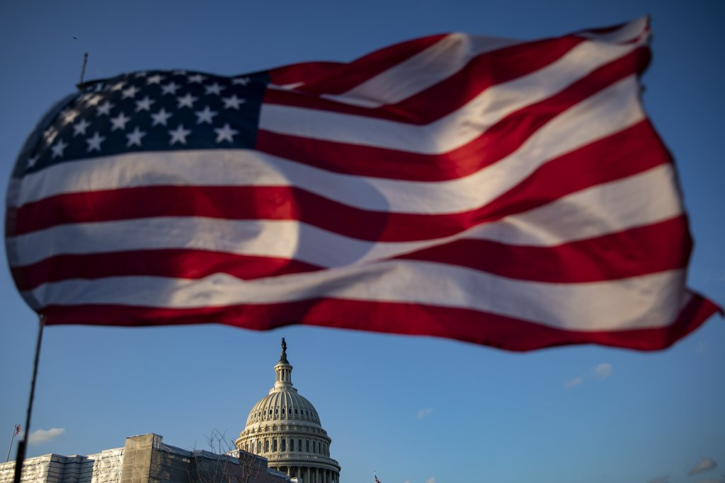 American flag flying with U.S. Capitol in the background.