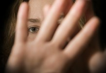 A woman holds her hands in front of her face.