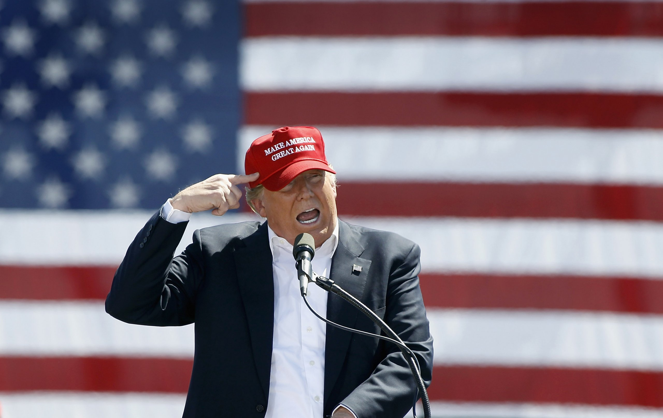 Donald Trump points to his head, wearing a red hat, and standing in front of an American flag.