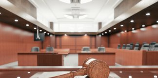 nterior of an empty courtroom with gavel and sounding block on the desk.