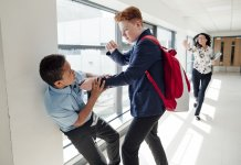 Redhead teenage male bullying mixed race teenage boy in the corridor at school.
