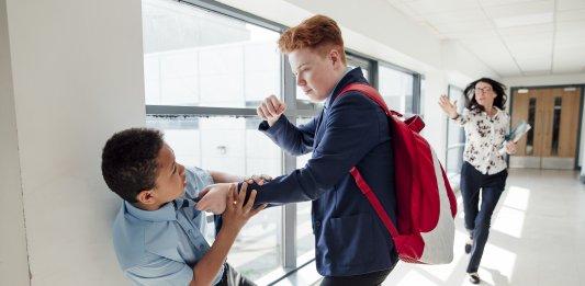 Redhead teenage male bullying mixed race teenage boy in the corridor at school.