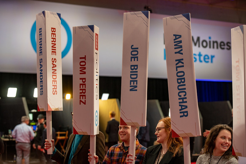 Students hold up tall, vertical signs with the names of presidential candidates.